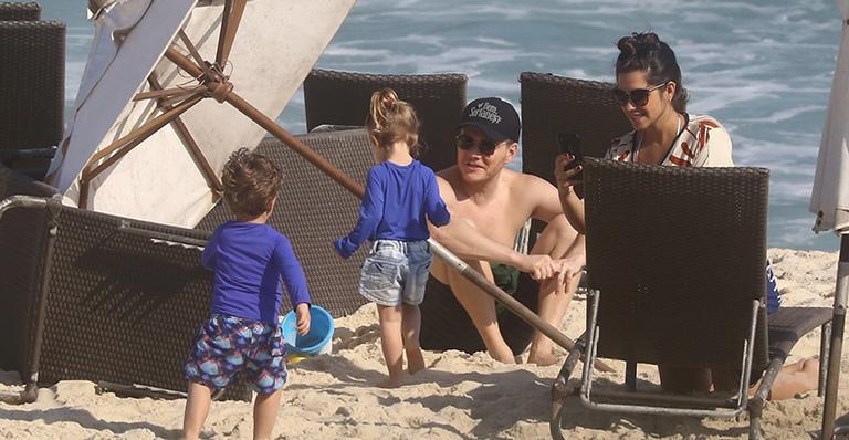 Atriz e cantor são flagrados durante brincadeira na praia com os filhos