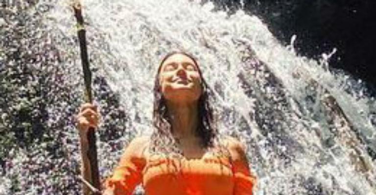 A atriz posou de biquíni se refrescando em meio à natureza